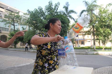 Người nhà bệnh nhân cầm chai, lọ xuống bể chứa nước để lấy nước về phòng dùng