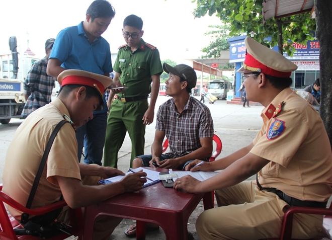 Tài xế Lê Văn Triều (ngồi giữa) bị Tổ CSGT lập biên bản vi phạm lỗi chở hàng hóa trong khoang hành khách.