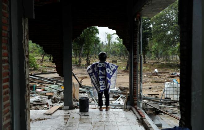 Ngườiđànông thẫn thờ nhìn ngôi nhà của mình bị tàn phá bởi sóng thần.Ảnh: Reuters