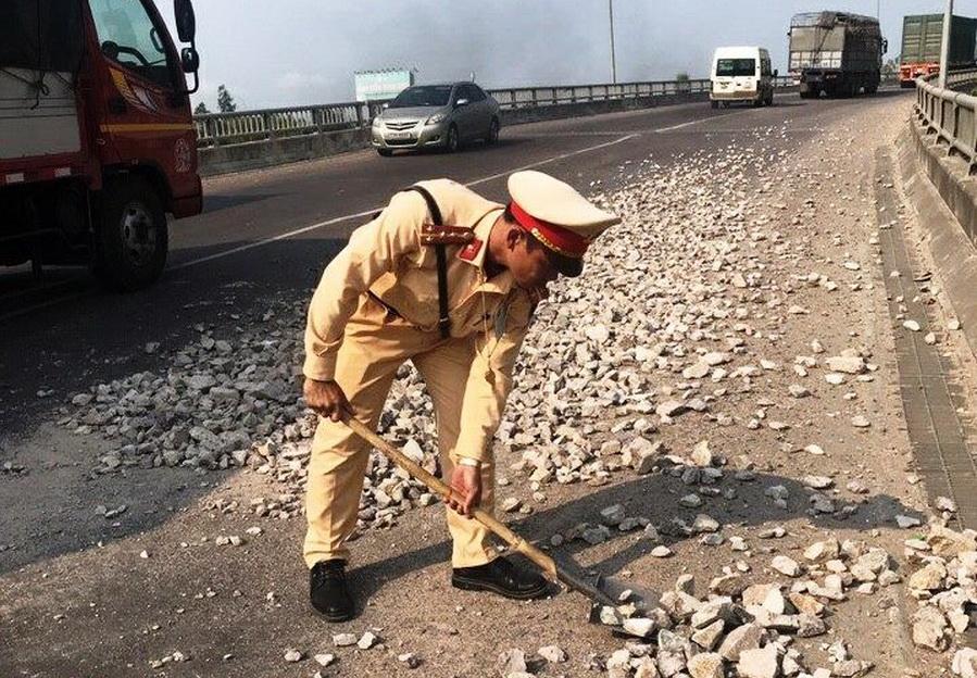 CSGT Công an tỉnh Bình Định thu dọn đá dăm rơi vãi trên đường