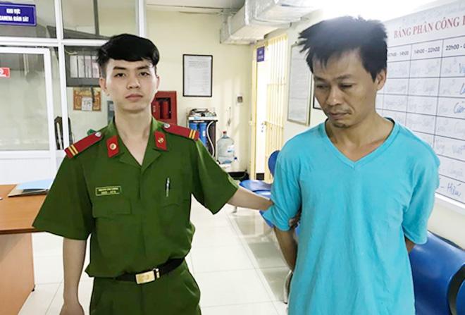 Cán bộ Công an áp giải Đinh Ngọc Minh vào nhà tạm giữ.
