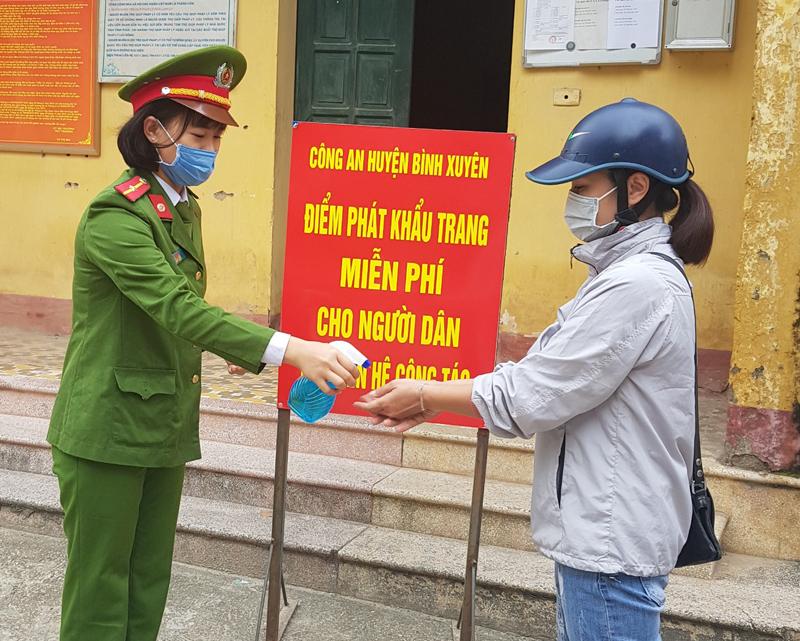 Thiếu úy Trần Khánh Mỵ khử trùng cho người dân đến làm việc.