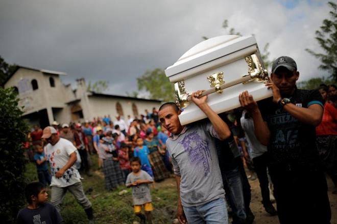 Những người hàng xóm và người thân thay nhau cõng chiếc quan tài màu trắng, dọc theo con đường làng lầy lội để đến một nghĩa trang nhỏ, nơi chỉ có bảy ngôi mộ màu xám.