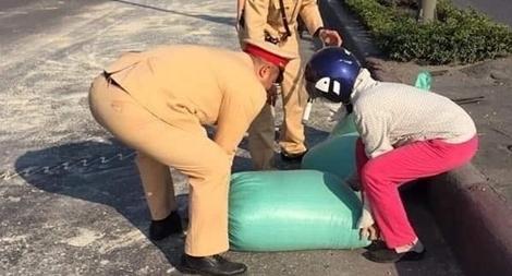 CSGT giúp lái xe thu gom 10 tấn ngô rơi trên đường