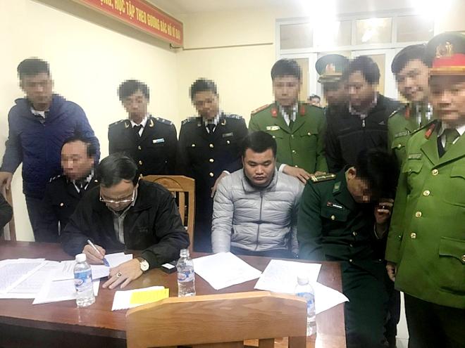 Nguyễn Văn Anh (ngồi giữa) bị bắt khi đang vận chuyển 120 bánh heroin qua cửa khẩu Cầu Tre.