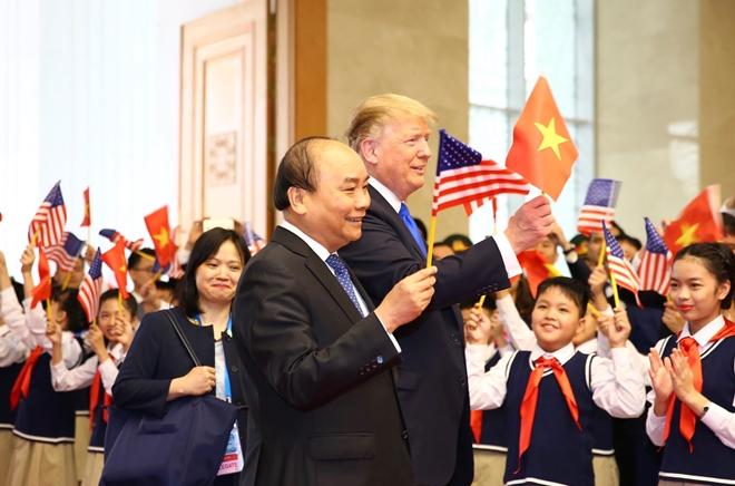 Hai nhà lãnh đạo cùng tươi cười vẫy lá cờ Việt - Mỹ trước đông đảo mọi người.