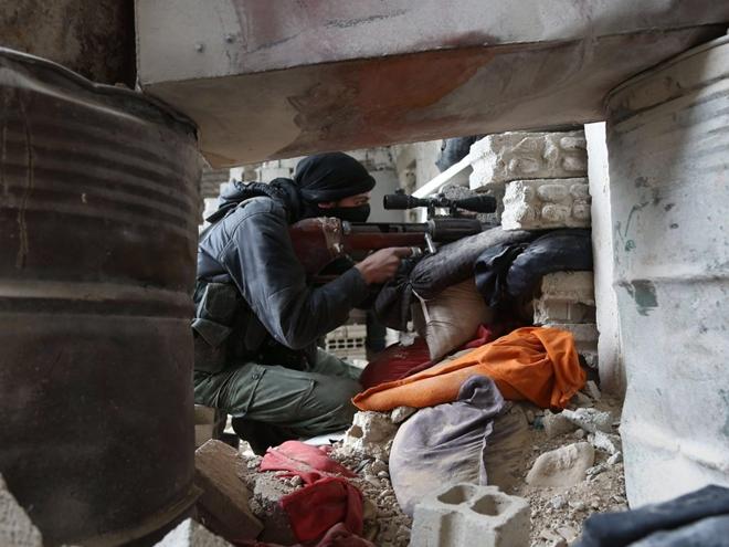 Một tay súng phiến quân ngắm bắn từ một tòa nhà đổ nát. Ảnh: EPA