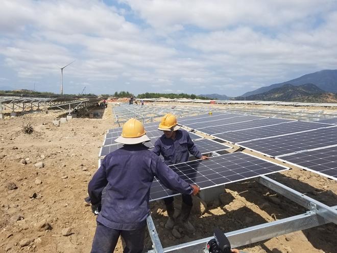 Lắp đặt các tấm pin cho dự án điện mặt trời phía dưới dự án điện gió.